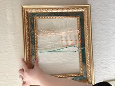 I had an old picture frame laying around the house that I really liked but was too fancy for any of my photos. I also had a tangled pile of necklaces on top of my dresser. Solution: I removed the glass and backing from the frame, hammered small holes into Necklace Display, Jewellery Display, Diy Jewelry, Jewelry Design, Old Picture Frames, Second Hand Stores, Visual Display, White Gold Jewelry, Jewelry Organization