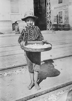 Νεαρός πλανόδιος πωλητής γλυκών στο λιμάνι. Δεκαετία 1910
