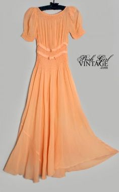 """$195 """"Here's a gorgeous vintage / antique long peach silk chiffon gown from the 30's art deco era. Smocked waist, puff cap sleeves have little padding to keep them full on top, grosgrain ribbon with bows in front, side metal snaps. Such old Hollywood glamor style! We love these when worn out as dresses with a slip underneath. It is a bit sheer so a nude colored or peach slip works best. This dress has no slip or liner with it."""""""
