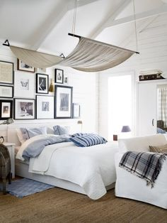 Coastal bedroom. Love the white with sisal rug, wicker chair, a bit of blue and black and white picture wall