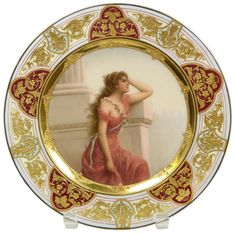 "ROYAL VIENNA PORCELAIN 'SEHNSUCHT' PORTRAIT PLATE  Antique Royal Vienna Austrian porcelain portrait plate. Depicts a young girl in pink dress staring off into the distance with a look of desire in her face. Titled ""Sehnsucht"" or ""Longing"". Signed Wagner to lower right of portrait. Stunning gilt work with enamel beading to border with pink, turquoise and cream backgrounds. Blue bee hive or Bindenschild mark to bottom."
