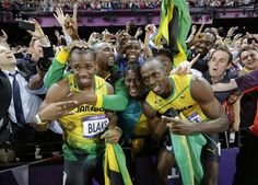 Jamaica's Usain Bolt, center right, celebrates winning gold in the men's 100-meter final with his mother Jennifer, center, and silver medallist Yohan Blake of Jamaica, center left, during the athletics in the Olympic Stadium at the 2012 Summer Olympics, London, Sunday, Aug. 5, 2012.