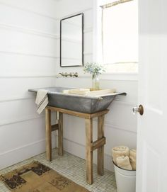 A simple wooden stand (and holes drilled for plumbing) transforms a Dutch galvanized metal hay-collecting bin into a statement-making sink in this California cottage's powder room.