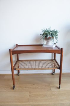 Manufactured in Denmark by G. S. Glyngore Stolefabrik in the 1960s. Made of teak veneer and wicker shelf. In overall excellent vintage condition. Manufacturers mark. Length: 70cm Width: 42.5cm Height: 59cm Please contact me prior to purchase for shipping quote.