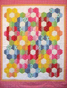 Charming bright 30's print Nana's Flower Garden ( strip piece assembly) , by Kathy Klassen 52in. x 45in.  Half hexagons