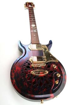 """Goulding Guitars from England. """"About Goulding Guitars The body of a Goulding guitar is made from a two inch thick billet of aluminium, which is machined from the rear to make it hollow. The front is machined to give it it's carved look. We have our own Goulding designed pickup surrounds made in Gold Plated Brass. The neck is also made from a solid billet of aluminium. The fret board is made of Cocobola or Birdseye Maple with mother of pearl, NZ paua or abalone markings """""""