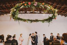 Floral chandelier wedding altar | Image: Luke Bugenske via Green Wedding Shoes