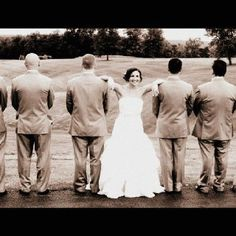 Bride with groomsmen only with flowers behind their back.
