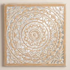 This striking piece of wall decor is hand carved by artisans in India in an intricate medallion design, finished with subtle whitewash and laid over a mirrored plaque.