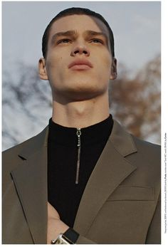 A sporty aesthetic is realized with the combination of a neoprene jacket and zip-up turtleneck from Prada.