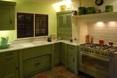 Green kitchen with louvred doors.