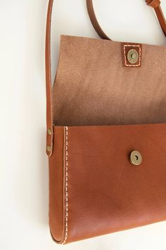 Look at this cute cross-body purse! This small purse is made of supple German leather in a dark cognac colour. An adjustable cross-body leather strap completes the purse.