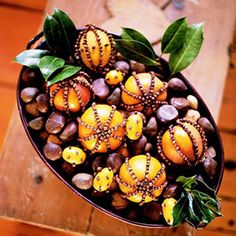 Nuts surround clove studded clementines and kumquats for a colorful and scent-sational centerpiece.