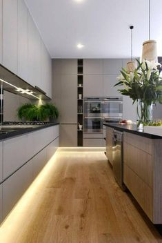 Modern kitchen design for a luxury interior via freshhouz. With on trend handle-less grey kitchen cabinets, wooden flooring, and built-in appliances, this is a beautiful example of a contemporary kitchen which combines style and functionality. Modern Kitchen Cabinets, Kitchen Cabinet Design, Kitchen Layout, Kitchen Flooring, Wooden Flooring, Kitchen Modern, Minimalist Kitchen, Grey Cabinets, Modern Room