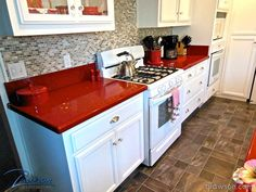 Kitchen remodel - White cabinets with smoked glass, polished silver hardware and red Caesarstone counter tops. By Lawson Construction.