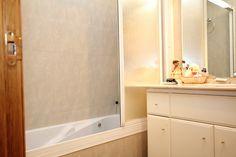Baño con bañera de hidromasaje,inodoro, lavabo con mueble y espejo.