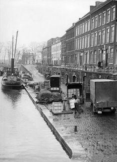 De oude haven, waar de vrachtwagens nog met de hand worden geladen. Maastricht, Nederland, 1930-1940.