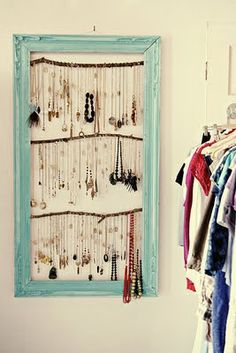A place to put all that jewelry.  An old frame and sticks from outside make this really cool necklace display.