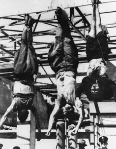 The bodies of Italian dictator Benito Mussolini, center, his mistress, Clara Petacci, right, and Achille Starace, former secretary of the Fascist Party, hang by their heels in Milan.   He was killed, along with his mistress Clara Petacci, by communist partisans on 27 April 1945, after being captured fleeing to Switzerland.