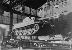 A newly bulit Tiger I heavy tank being loaded onto a rail car at the Henschel factory in Kassel, Germany, 1942-1944. The fender skirts are not installed at the factory as they would cause the tank to be too wide for rail transport.  Also a completed Panther in background.