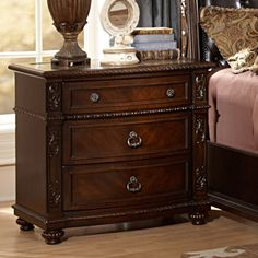 Visually stunning, this elegant nightstand from our Oakmont Manor Collection exudes luxury and grandeur. The detailed acanthus leaf carvings and egg dart molding lend in this nightstand's affluence.<br>...