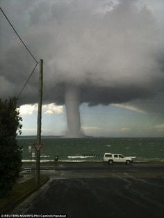 In deep water: A car races on ahead as this waterspout appeared close to the shoreline at Batemans Bay, 140 miles south of Sydney