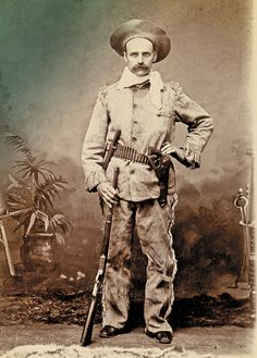 "In this circa 1880-90 cabinet card, this frontier type poses with the two marque firearms that later were claimed to have ""won the West."" The gent holds a Winchester Model 1873 lever-action carbine, while a Colt Model 1873 Single Action Army revolver resides in his open-topped belt holster. (The long-cased cartridges in his belt would fit neither weapon.)  – Courtesy Dickinson Research Center, National Cowboy & Western Heritage Museum, RC2006.038 –"