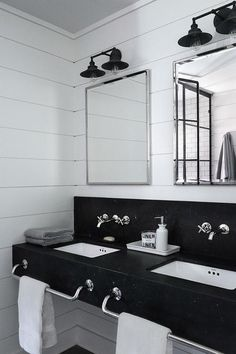 Black and white industrial bathroom features a honed black marble floating dual vanity accented with built in polished nickel towel bars and square undermount sinks positioned under polished nickel faucets mounted on a honed black marble backsplash.