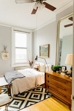 love pretty much everything. vintage dresser, large mirror, geometric rug, barely gray walls.