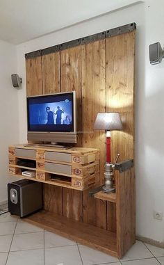 Let us start with the furniture piece for the decoration of the TV launch, here you can see the reclaimed wood pallet made TV stand and wall art. It is an amazing idea because it offers the storage of DVD player, offers a place to place the TV and adorns the wall as well.