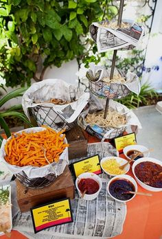 A DIY french-fry station served in metal baskets with assorted dipping sauces.