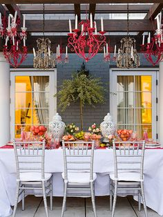 This outdoor dining room has an elegant and fun feel thanks to brightly painted chandeliers that hang from pergola beams. Simple silver chairs and a white tablecloth keep the table from feeling too overpowering with its bold runner.