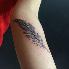 small eagle feather tattoo on arm