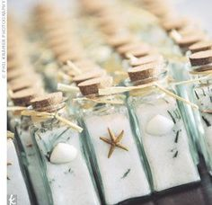Glass spice bottles decorated with starfish and seashells had been filled with homemade rosemary-infused sea salts as favors.