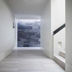 Shared formal entry at the Walsh Street Apartments by B.E Architecture with bluestone wrapping into into interiors.