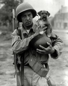 Pfc Joseph E. Day holds a puppy in a German helmet, Le Dezert, France, 1944