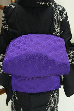 こっくりとした深紫色に光の加減で浮かび上がるように織り出された麻の葉模様が粋な開き名古屋帯です。