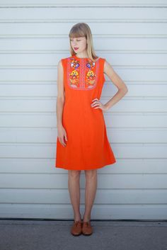 """vintage bright orange cotton shift dress with embroidered bib front depicting flowers, birds, and cacti. bust darts at front, metal zipper at back. light staining across the front at various places, hardly shows in photos.shoulders: 15""""bust: 19""""length: 38""""model is a size 2.please note that everything in my shop is used or vintage, and that minor flaws are to be expected. everything has been gently worn and the prices reflect their condition. p..."""