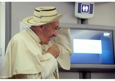 Pope Francis wears a sombrero from Panama which was donated to him by a journalist on board the flight from Krakow, Poland, to Rome, at the end of his 5-day trip to southern Poland, Sunday, July 31, 2016 - AP