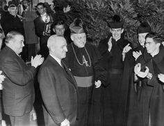 The chief Executive...President Harry S. Truman is applauded by Seminarians Brighton residence of archbishop Richard Cushing, who stands by the president. Also on hand were Gov. Paul Dever (left) and Congressman John F. Kennedy (behind the Archbishop). An estimated [?] persons greeted the President as his motorcade drove through. Date Photographed:17 October 1952