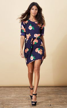 Navy drop back dress with a pull in tie waist and bold floral print.  Shop now.
