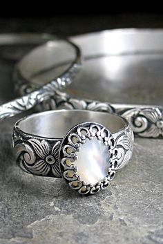 A shimmering mother of pearl cabochon is set on a flowering dogwood pattern band. Accented with a filigree setting, this ring is just the right size for every day wear, not too big, and not too small! Here in the Tennessee mountains, white dogwoods bloom everywhere in the spring, and this ring is a tribute to the lovely old tree in the garden behind my studio.