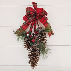 Welcome this winter season with this classic pine cone door swag! Made with 3 JUMBO pine cones adorned with faux green pine and clusters of red berries and greenery hanging from festive plaid flannel ribbon. The pine cones rang in size between 6 - 8 inches in length. The overall length of swag measures approximately 22 inches. Ive included a loop behind the bow for easy hanging. This swag is perfect for decorating indoors and out! Check out all of our Christmas Decor…