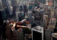 ranch base jumper Florian Pays gestures while leaping from Malaysia's landmark, 1,389-foot high KL Tower in Kuala Lumpur. (Vincent Thian/Associated Press)