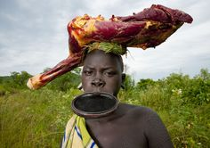 Ethiopia - This girl was coming back from a market with some meat on her head. As cow is precious thing in Surma tribe, like in Massai, people eat meat only for special events. Indigenous Peoples Day, Mursi Tribe, Eric Lafforgue, Tribal People, We Are The World, Big Lips, World Of Color, Namaste, Bring It On