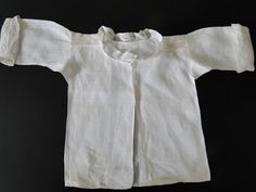 Infant's shirt, 18th century. Linen with Hollie Point insertions on the shoulder with a design of flowers and hearts, fine whitework embroidery along the edges of the insertions and on the cuffed sleeves.