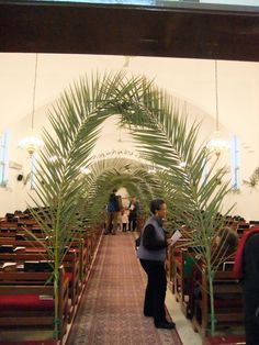Palm Sunday decorations - This many arches would block the view of the pastor.  Maybe make an arch behind the altar? Use something heavy that won't tip and attach firm, shapeable wire to each side.   Wire palms onto arch wire so that they hide the wire and meet in the center.
