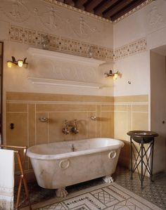 The coffered ceiling and beautifully tiled floor both bring Roman influence to an otherwise Greek inspired bathroom. The low relief frieze is supported by ornate molding and that epic marble tub. There's also the entablature of the built in niche shelf to correspond with the frieze.