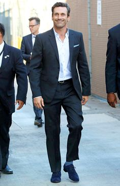 Jon Hamm cut a dapper figure in a black suit, white button up shirt, blue striped socks, and a pair of blue shoes while out and about in L.A.