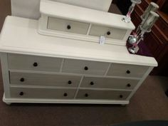 $250 - This Unique dresser is 2 piece construction, the upper two drawers may be removed. Seven drawers in the base two additional drawers on top. It has been painted a creamy white quit smoky drawer fronts and black Hardware. The chest measures 57 inches across the front, 18 inches deep. The base of the dresser stands 30 inches tall with the addition of the top two drawers it is 38 inches tall. It can be seen in booth H 13 at Main Street Antique Mall 7260 East Main St ( E of P...